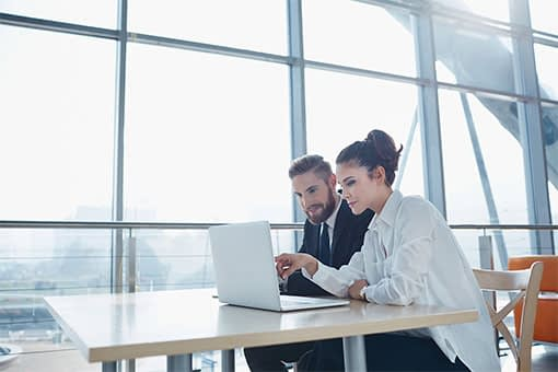 Man and woman from restaurant accounting team reviewing financial statements on shared laptop computer in modern office