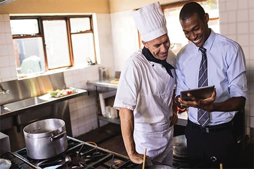 Young restaurant manager sharing screen on tablet device with seasoned chef in restaurant kitchen