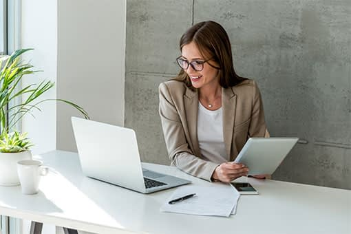 Businesswoman in blazer holding a tablet and smiling while looking at her laptop screen in a sunny, modern office