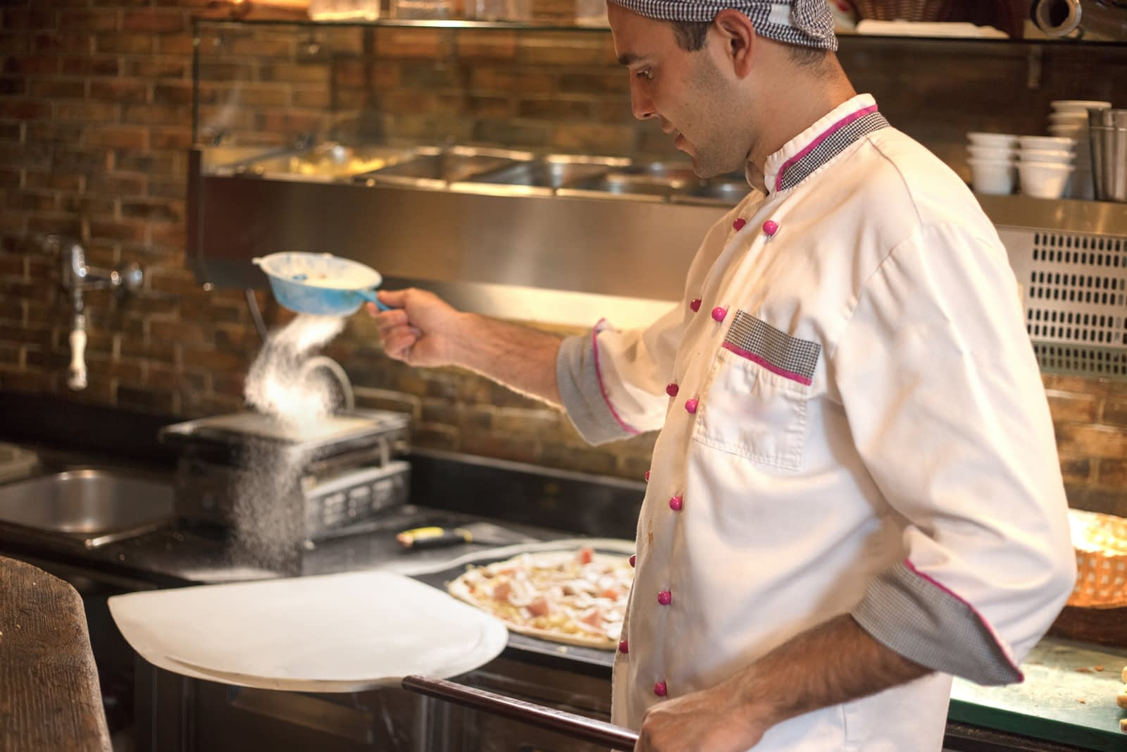 A restaurant chef sprinkles flour on pizza dough on pizza paddle