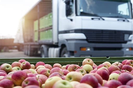 Large crates of red apples sitting in front and inside of a parked semi truck