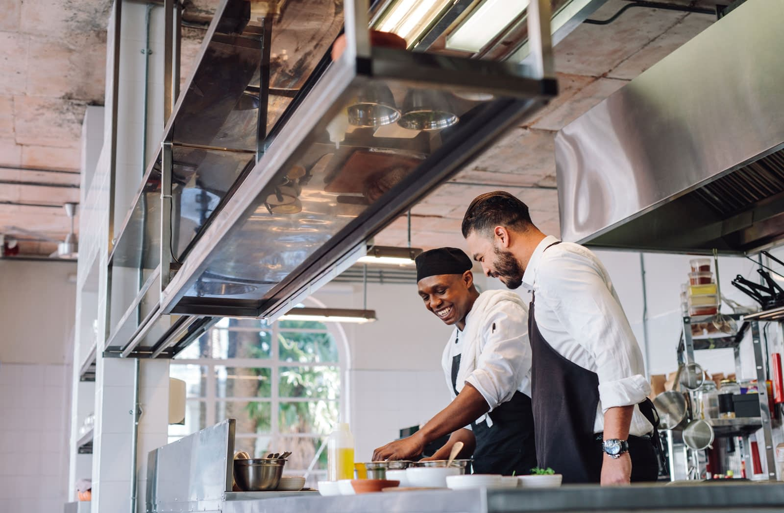 Two male restaurant chefs smiling while preparing a sauce together in modern restaurant kitchen