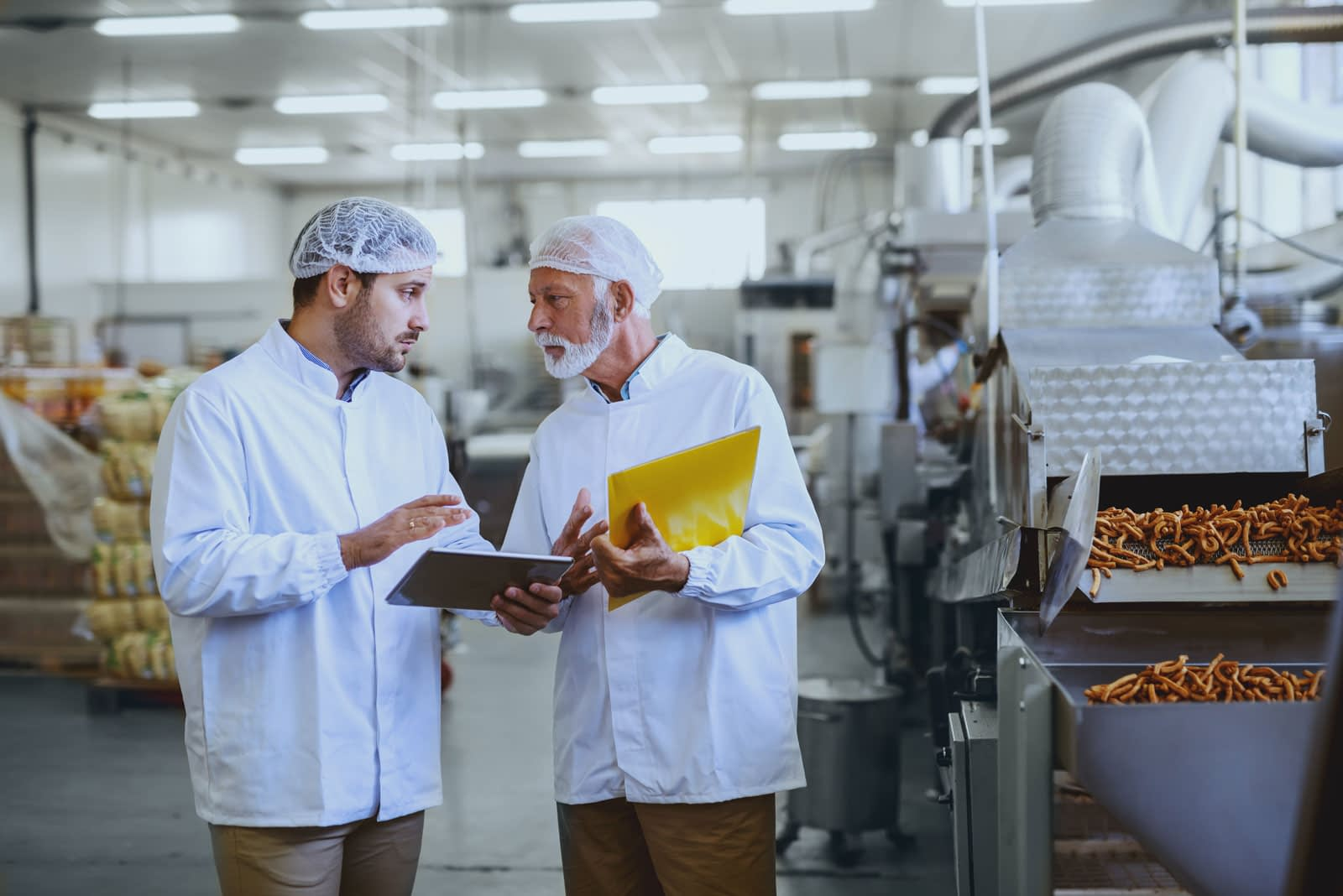 Two men in a food processing plant discussing operations next to a machine producing french fries