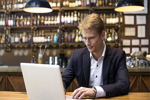 Male restaurant manager in blazer reviewing data dashboards on laptop at restaurant bar